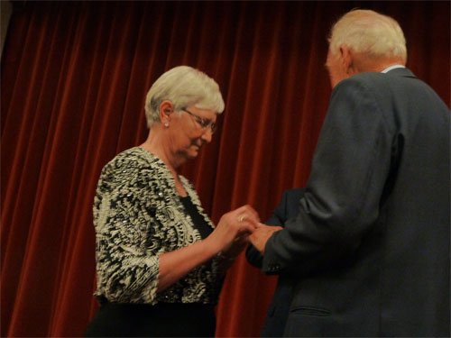 Photo of Dianne placing ring on Bob's finger