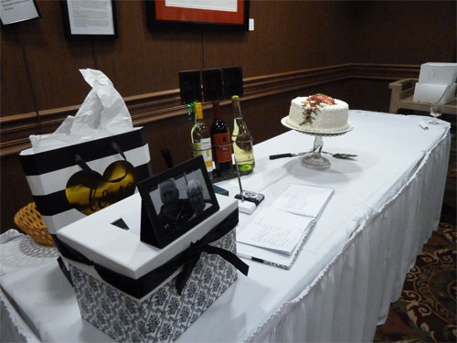 Photo of table with guest book, card box, and cake